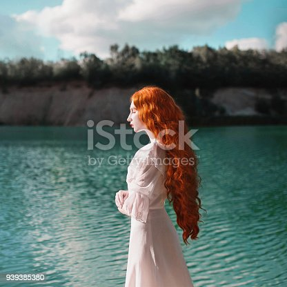 Beautiful red-haired woman in a luxurious renaissance dress on the background of a lake with blue water