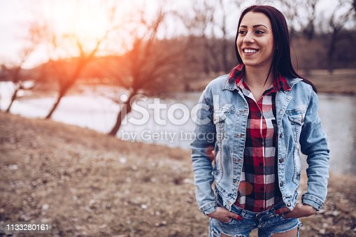 Beautiful redhead woman  walking and having fun by the river, its early spring time, end of the day.