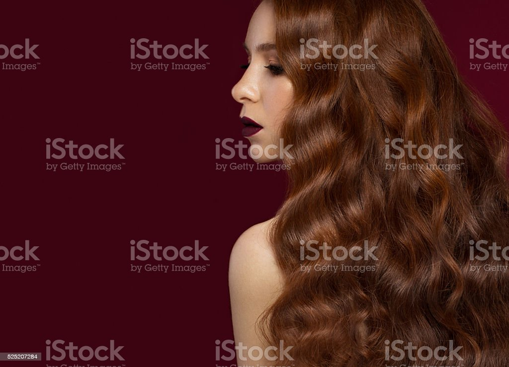 Beautiful Redhead girl with  perfectly curls hair and classic make-up. stock photo
