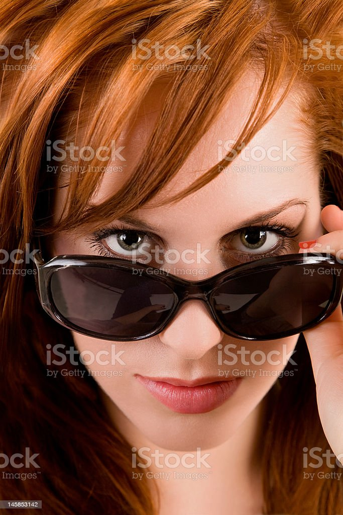 Beautiful Redhead Lady Looking Over Sunglasses royalty-free stock photo