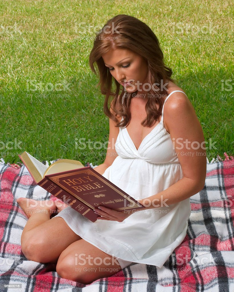 Beautiful redhead woman reading Bible on green grass outdoors royalty-free stock photo
