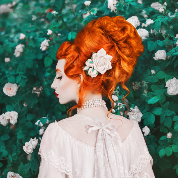 Beautiful redhead woman with high hairdo in a white dress on rose background. Portrait of young unusual pale girl with red hair. Beautiful model with stylish hairdo with a rose in garden stock photo
