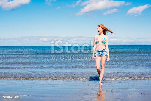 Beautiful redhead young woman walking out of the sea on a beautiful summer day. Caucasian teenage girl in bikini top and cut of jean shorts with long red hair paddling in shallow water on beach.