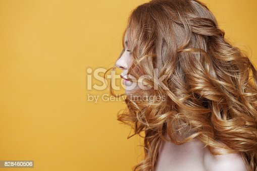 istock Beautiful redheaded girl with luxurious curly hair. Portrait in profile. Free space left. Studio portrait on yellow background. 828460506