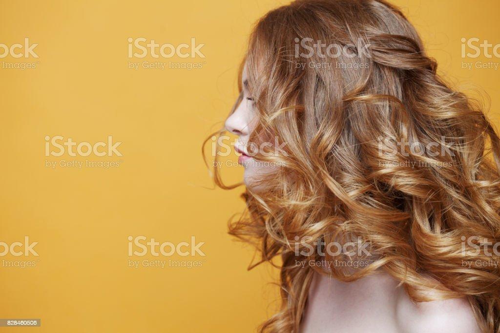 Hermosa chica pelirroja con el pelo rizado lujoso. Retrato de perfil. Espacio libre izquierda. Retrato de estudio sobre fondo amarillo. - foto de stock