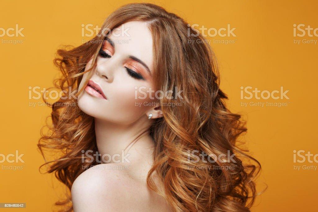 Hermosa chica pelirroja con el pelo rizado lujoso. Retrato de estudio sobre fondo amarillo. Excelente pelo - foto de stock