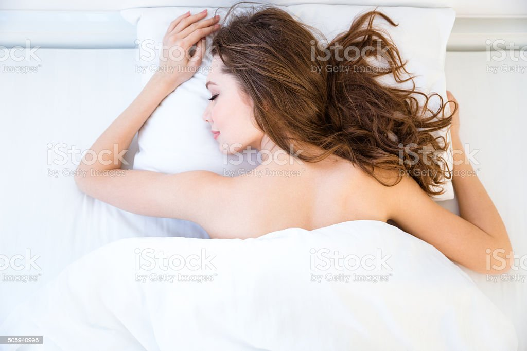 Beautiful relaxed woman lying and sleeping on bed in bedroom stock photo