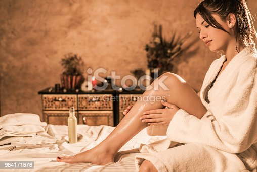 Beautiful relaxed young woman in bathrobe putting lotion on her skin.