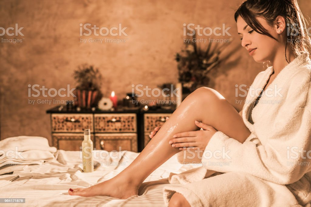 Beautiful relaxed young woman in bathrobe putting lotion on her skin. stock photo