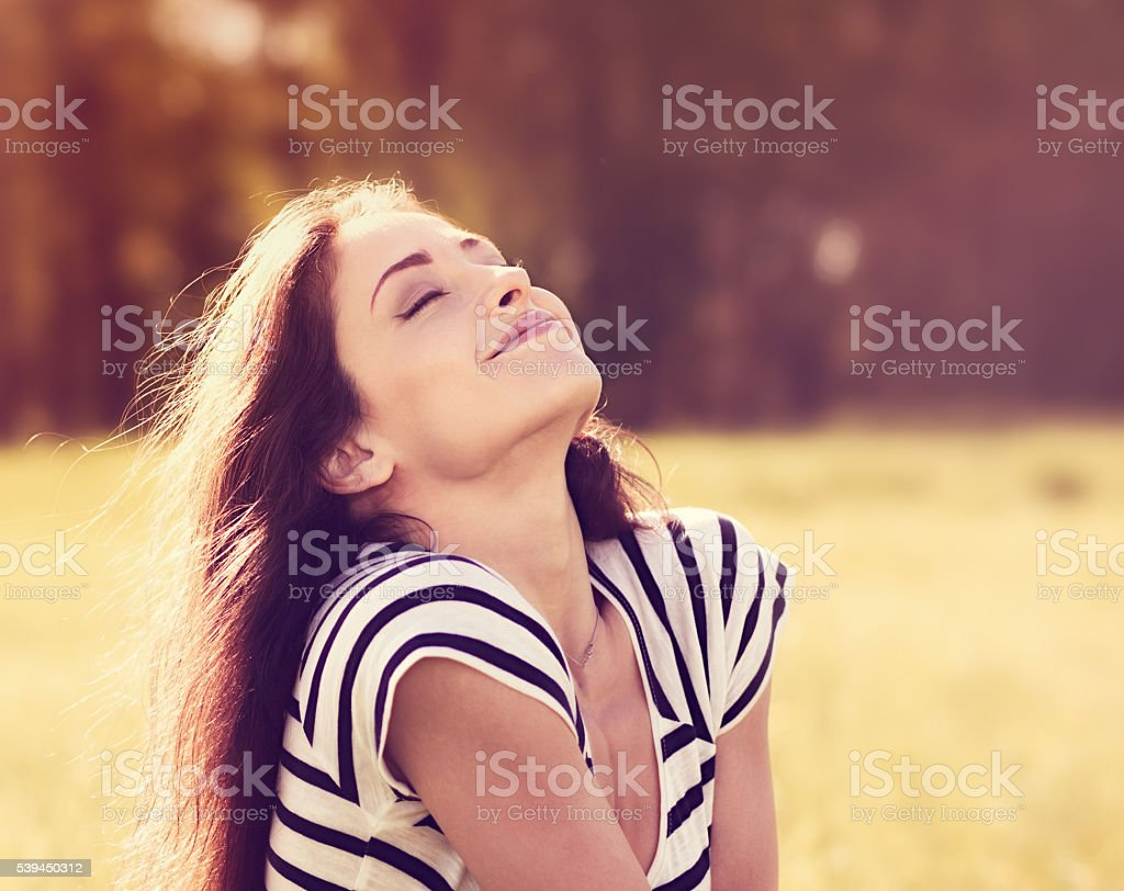 Beautiful relaxing woman sitting on the grass  and enjoying fres stock photo