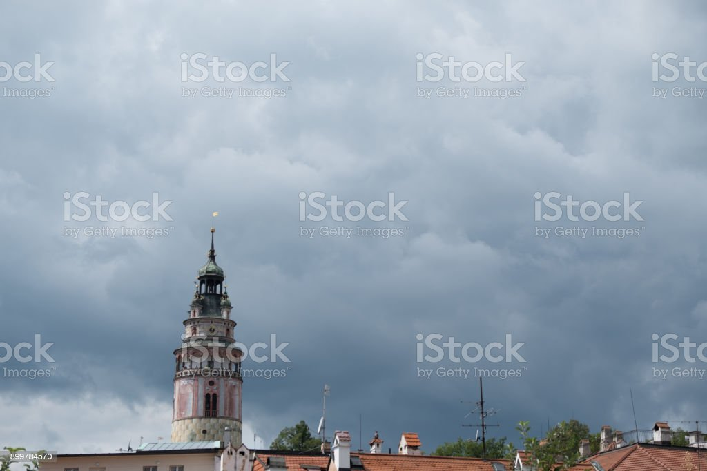 Beautiful Renaissance Castle Tower elaborately decorated with frescos against a stormy sky in charming medieval town of Cesky Krumlov. Castle Tower on the left room for copy space, cloudy sky. stock photo