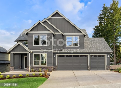 istock Beautiful residential home exterior on bright sunny day with green grass and blue sky 1209941784