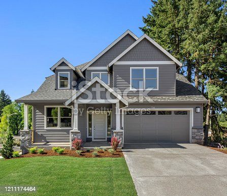 istock Beautiful residential home exterior on bright sunny day with green grass and blue sky 1211174464