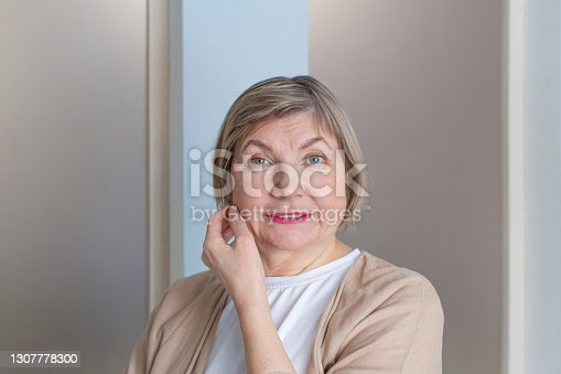 Beautiful senior woman with gray hair smiling is looking at the camera against on the background of home interior. Concept Anti age