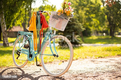 Beautiful turquoise bicycle parked in a park. Different color fashion bags are hanging on a governor. Summer flowers in bicycle white basket.