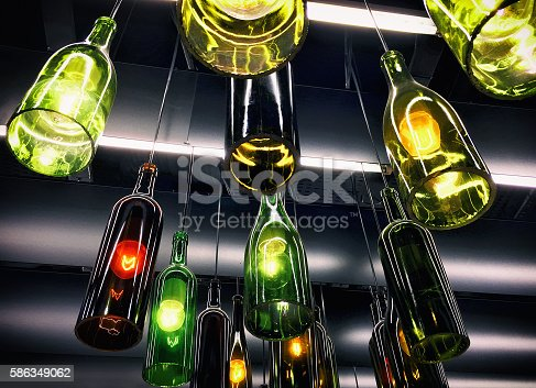 940992564 istock photo Beautiful retro light lamps decoration made of the wine bottles 586349062