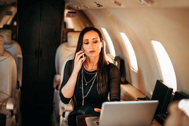 Beautiful rich and powerful woman working on a laptop and talking on a smart phone at the same time while flying on a private jet Beautiful rich woman talking on a smart phone while flying on a private airplane. She is working on a laptop. status symbol stock pictures, royalty-free photos & images