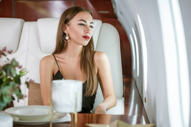 Beautiful rich woman in a private first class plane stock photo