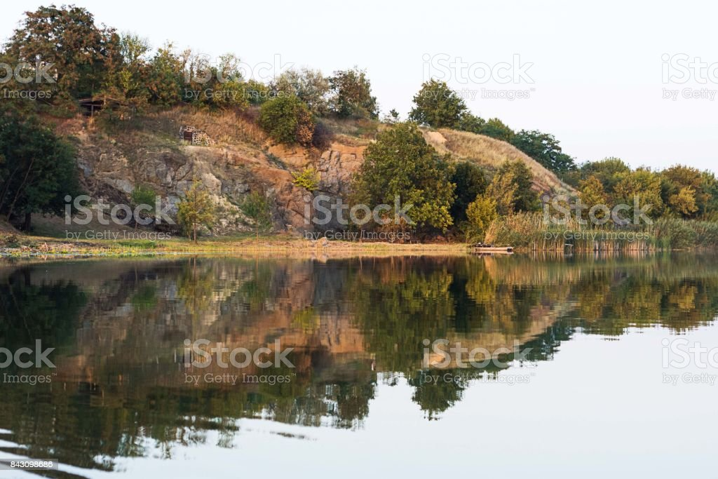 Beautiful riverfront scenery of calm water and part of forest stock photo