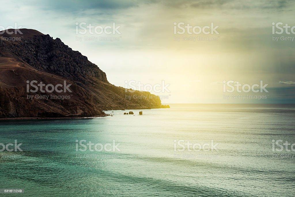 Beautiful rock on sunset sea background stock photo