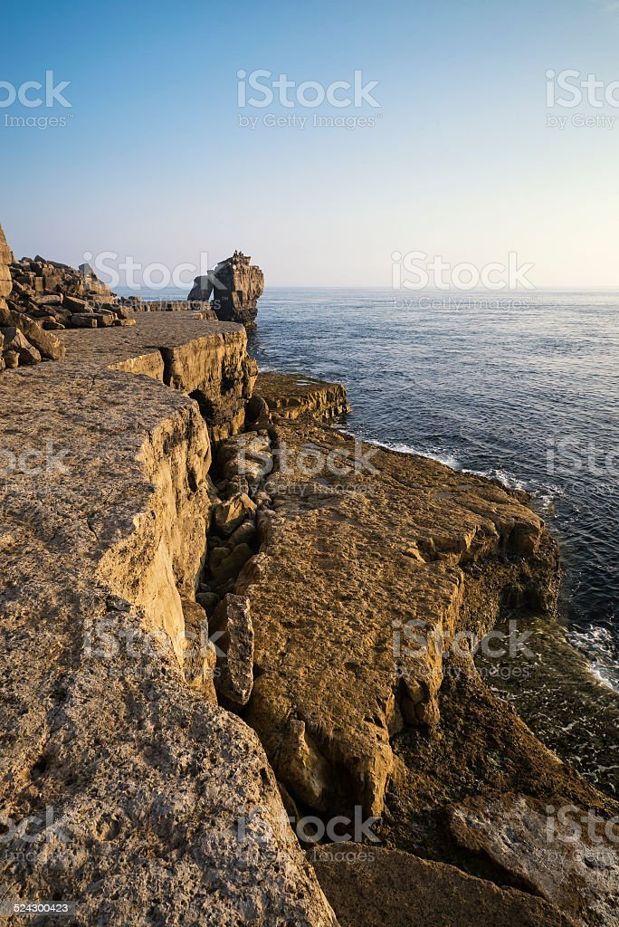 Beautiful rocky cliff landscape with sunset over ocean stock photo