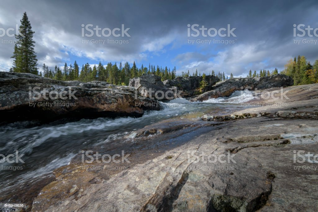 Beautiful rocky waterfall in sweden in magic pine forest landscape stock photo
