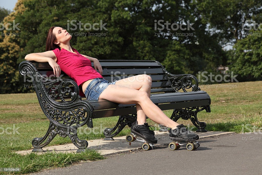 Beautiful roller skater woman sun tans in the park stock photo