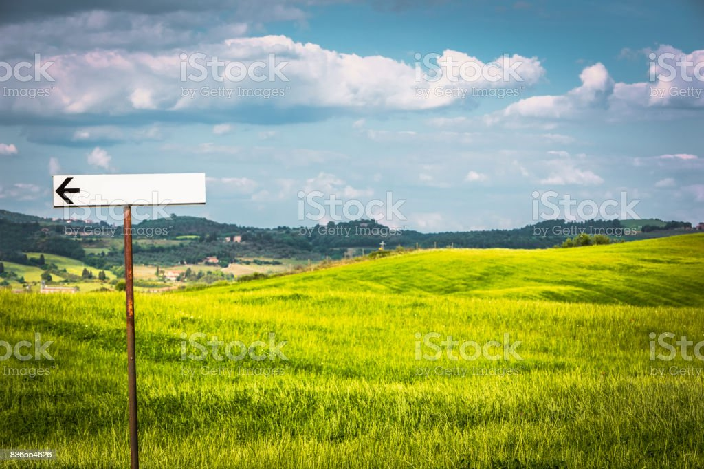 Beautiful rolling landscape. Green meadows of Tuscany, Italy. Empty road sign, copy space stock photo