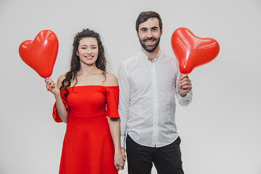 Beautiful romantic couple isolated on white background. An attractive young woman and beautiful hands raise balloons in the shape of the heart. Smiling. Valentine's Day!