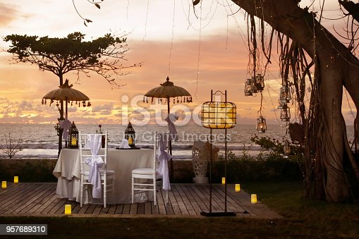 istock Beautiful romantic dinner set up, sunset time, tropical style 957689310