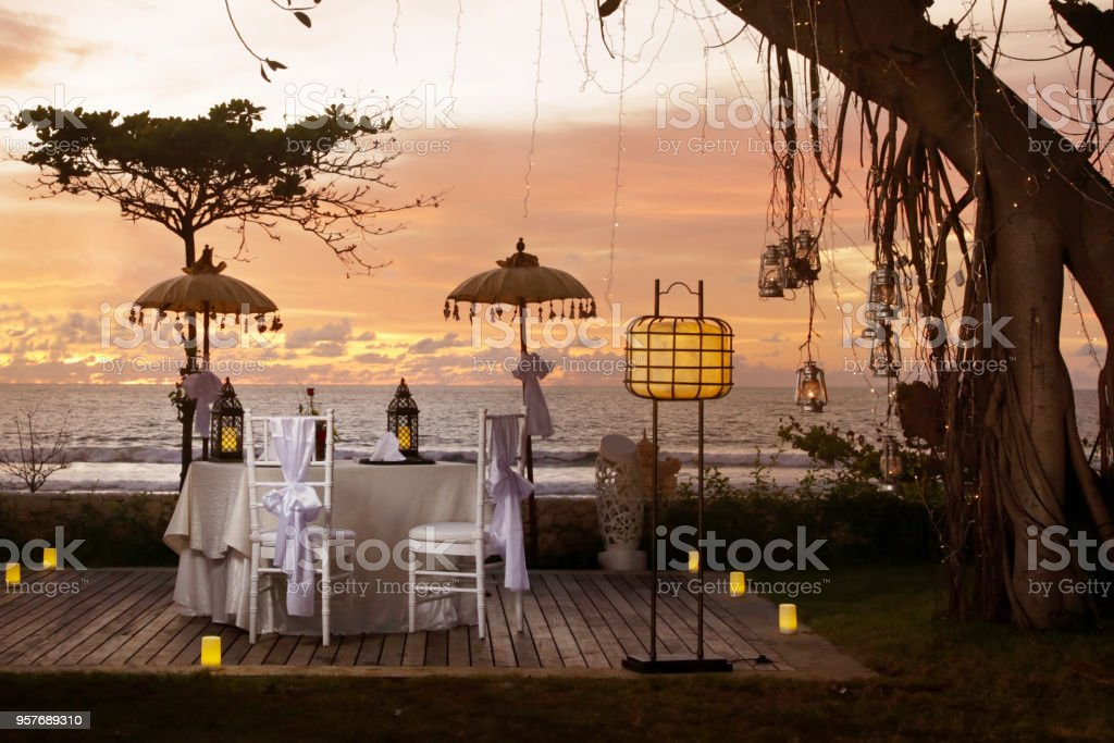 Beautiful romantic dinner set up, sunset time, tropical style stock photo