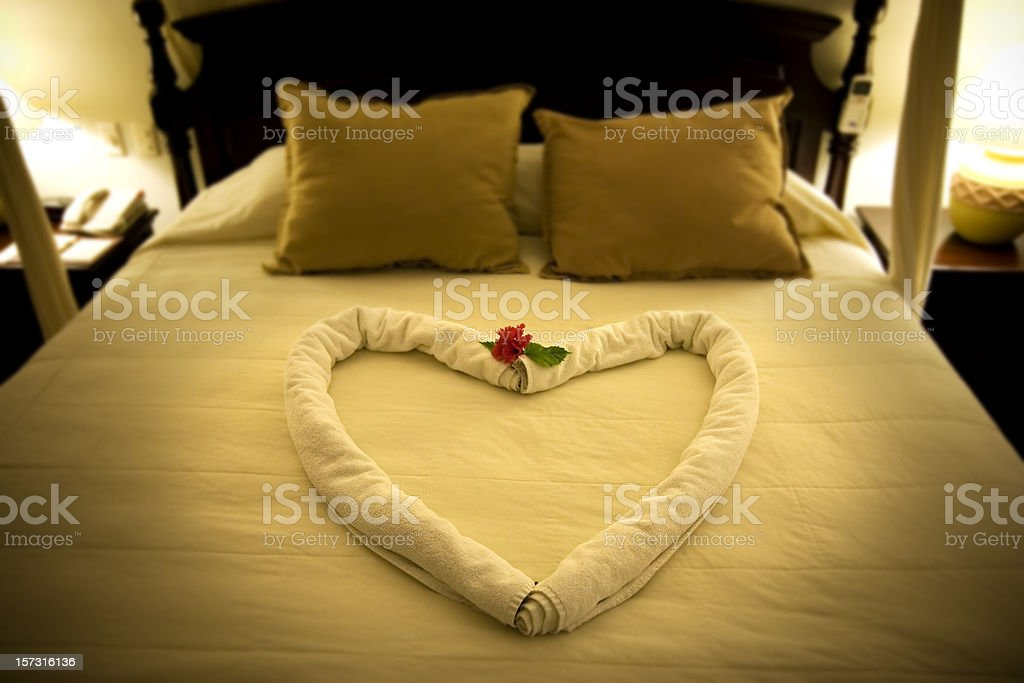 Beautiful Romantic Honeymoon Hotel Suite Bed with Heart Shape Towels royalty-free stock photo