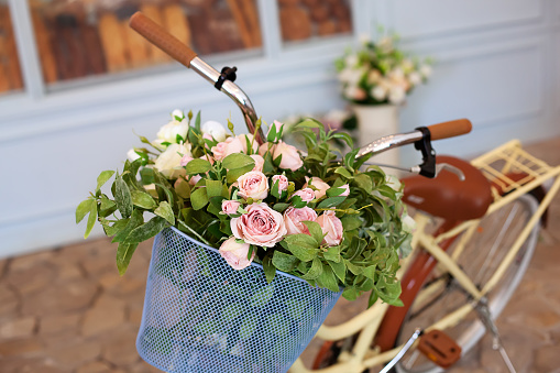 Beautiful romantic landscape: vintage wicker basket with flowers near the café. Old bicycle with flowers in a metal basket on the background of a bakery or coffee shop against the blue wall.
