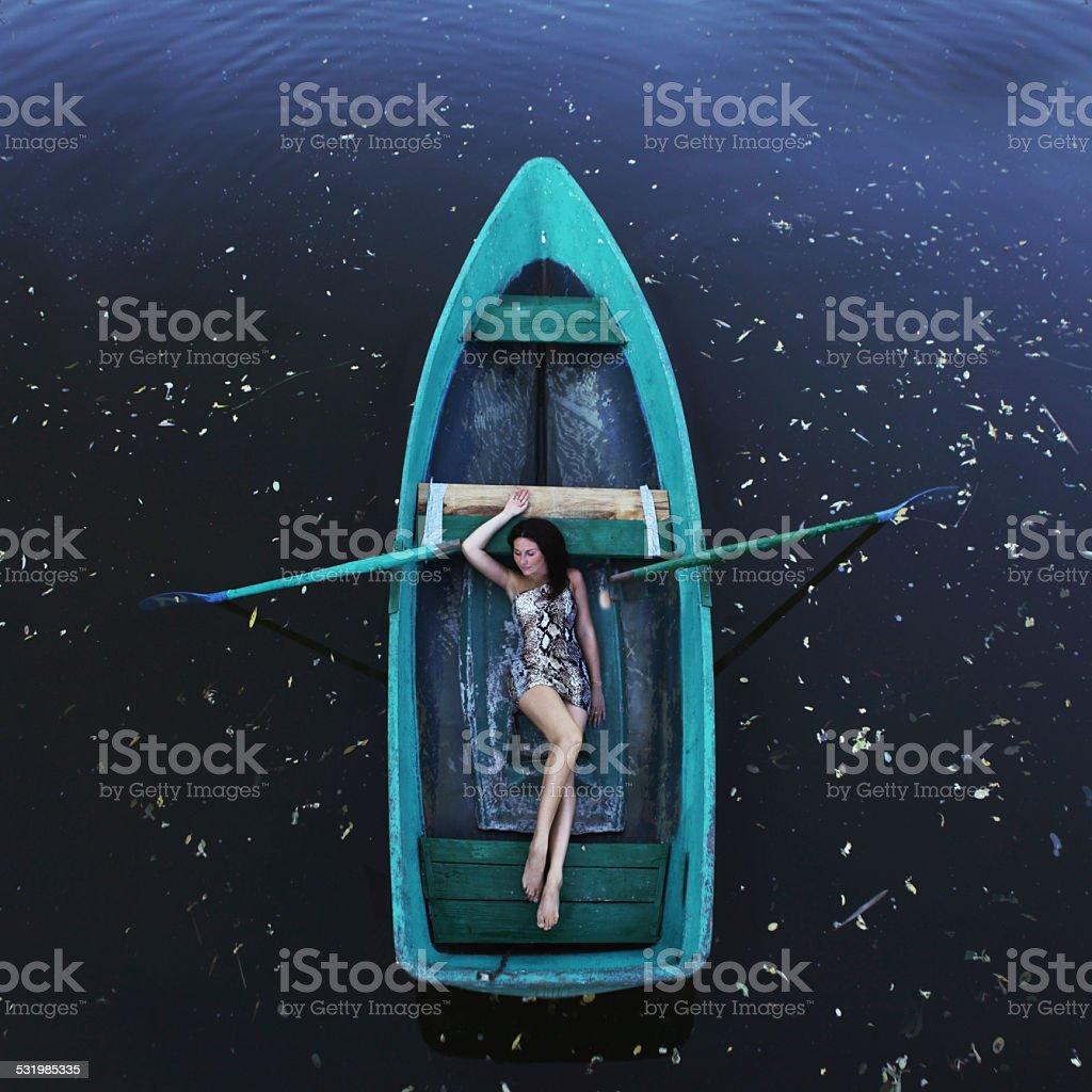 Beautiful romantic woman in a boat stock photo
