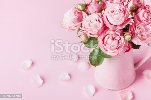 istock Beautiful rose flowers in pink vase for Womens day or Mothers day vintage greeting card. 1079764754
