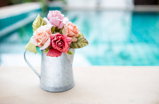 Beautiful rose paper flower in metal pot over blurred swimming pool picture id1047377488?b=1&k=6&m=1047377488&s=612x612&w=0&h=mv4fyefrjmpmwvgsasiamggxms6qaea zcpdd7c3ojo=