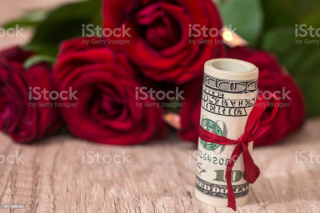 beautiful roses with money on desk stock photo