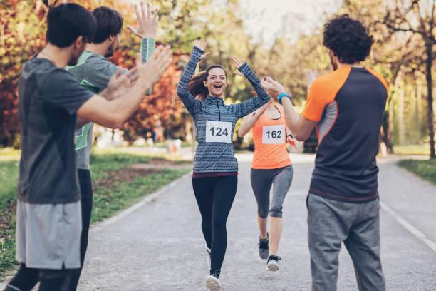 schönen läufer begrüßt das team von finish line - laufveranstaltungen stock-fotos und bilder
