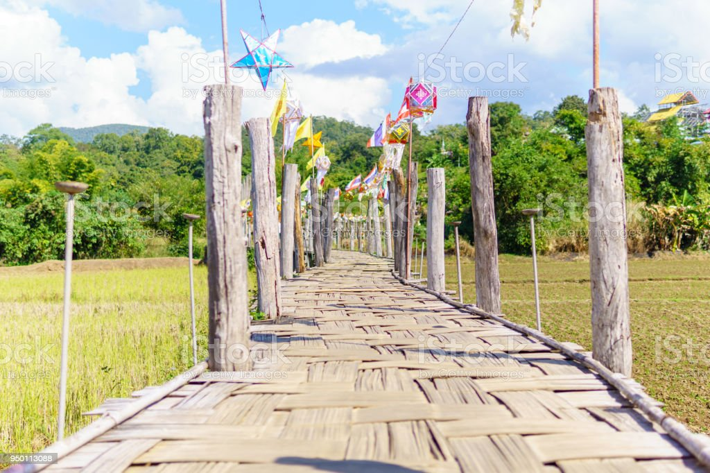 beautiful Rural bamboo bridge across the rice paddy fields with blue sky and fluffy cloud in sunny day at countryside.  Su Tong Pae Bridge,Mae Hong Son,Thailand. stock photo
