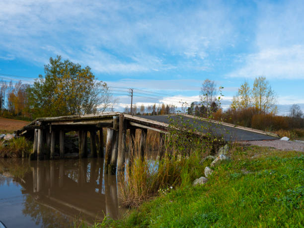 A beautiful rural scene with an old wooden bridge casting reflections on the calm river surface. stock photo