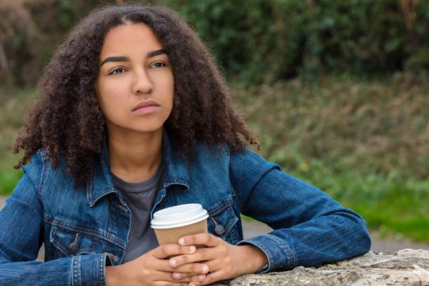 Hermosa triste deprimido o reflexivo raza mixta biracial afroamericana adolescente adolescente mujer joven mujer joven beber café fuera descansando en una pared - foto de stock