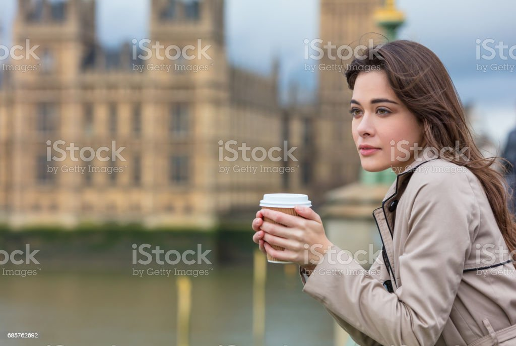 Beautiful sad, depressed or thoughtful young woman in London on Westminster Bridge over the River Thames drinking takeout coffee by Big Ben - foto de stock