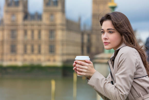 Beautiful sad, depressed or thoughtful young woman in London on Westminster Bridge over the River Thames drinking takeout coffee by Big Ben - foto de acervo