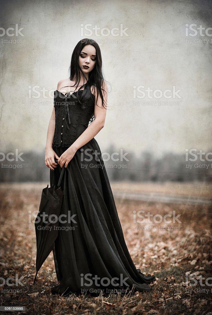 Beautiful sad goth girl holds black umbrella. Grunge texture effect stock photo