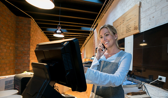 istock Beautiful saleswoman registering a takeout order while talking with the customer on a smartphone looking happy 931275746