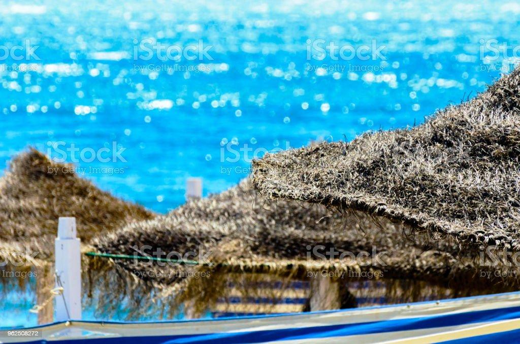 Bela praia com guarda-chuvas de árvore de palma e o azul do mar - Foto de stock de Areia royalty-free