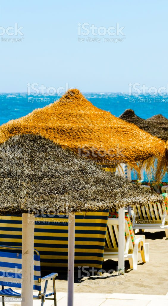 Beautiful sandy beach with palm tree umbrellas and blue sea - Royalty-free Bay of Water Stock Photo