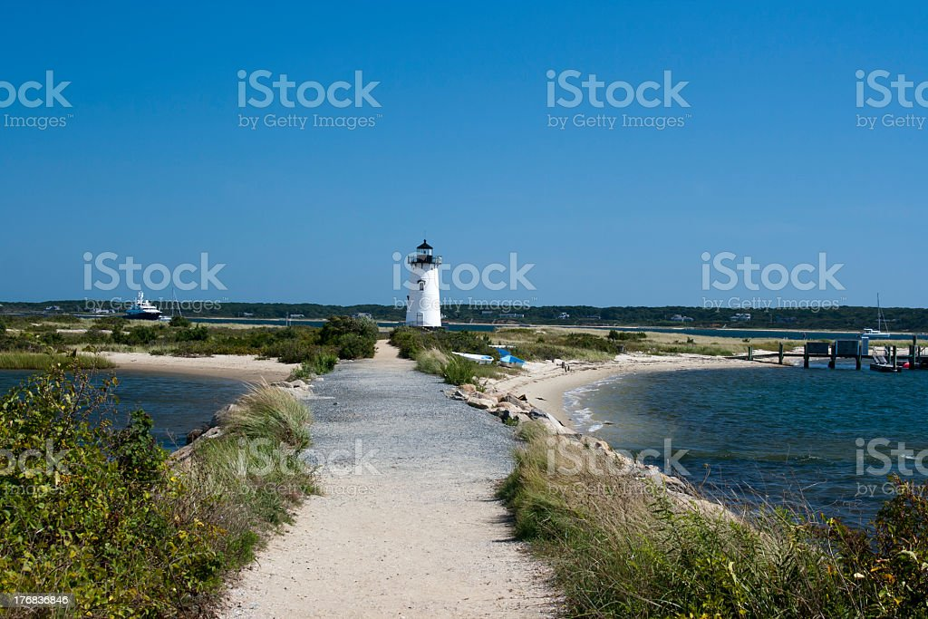 Beautiful sandy ocean path leading to a lighthouse stock photo