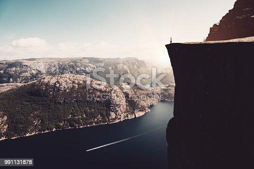 The alone woman standing on the preikestolen rock.