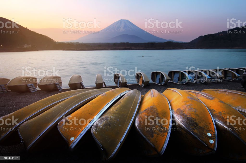 Beautiful scenery during sunrise of Lake Shojiko in Japan with the rowboat parked on the waterfront and Mountain Fuji background. Travel and Attraction Concept royalty-free stock photo